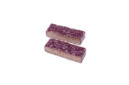 two slices of chocolate coated wafer with nuts lie on a white background