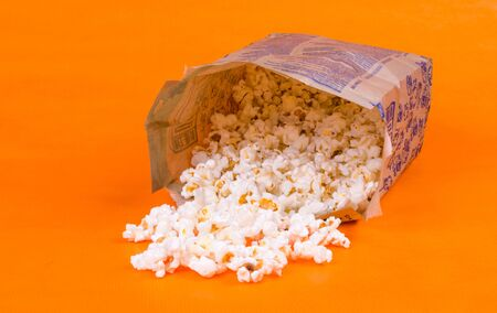 Side view of a pile of fried popcorn in a paper bag on an orange background