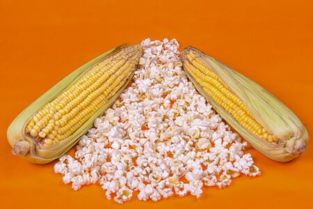 raw corn lies on a heap of fried popcorn, background is bright, orange, side view Фото со стока
