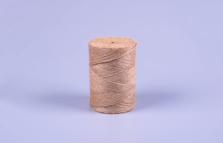 a coil of thin rope of brown color for packing boxes, background gray side view, closeup Фото со стока