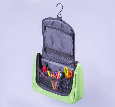 open green bag with school supplies, gray background side view