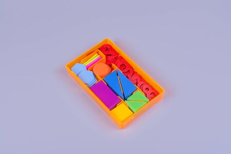 set for preparation for school, in a set of mugs, triangles, squares, sticks and figures from plastmasy, top view on a gray background
