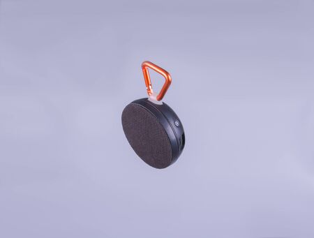black, wireless speaker with orange carabiner on a gray background side view