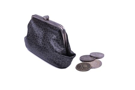 A pile of coins lies next to a gray leather wallet on white Фото со стока