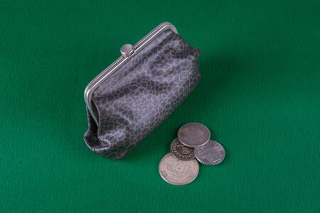 next to a gray leather wallet is a bunch of coins, photo on a green background, top view