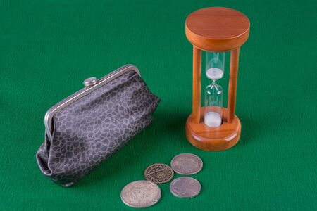 wooden hourglass, wallet and old coins are scattered on a green background, top view Фото со стока