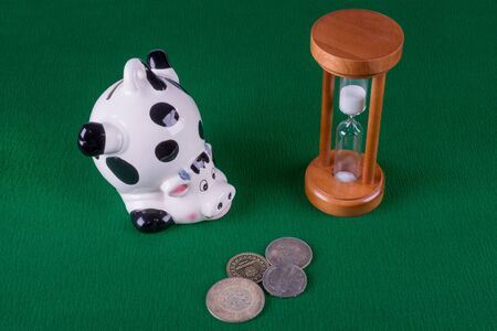 porcelain piggy bank in the form of a pig, old coins and a wooden hourglass lying on a green background, top view