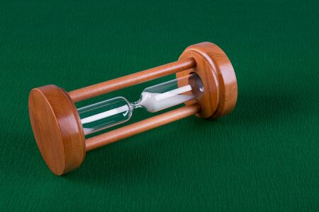 wooden hourglass lie on a green background, closeup photo, top view