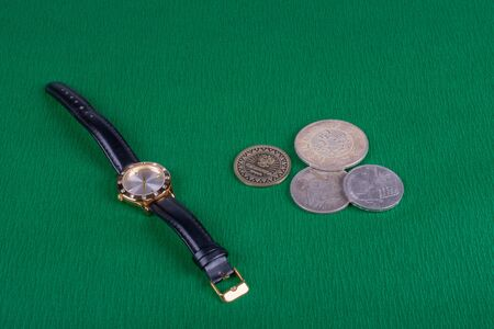 on a green background are womens watches with a black leather strap, and next to them are a bunch of coins, closeup photo, side view