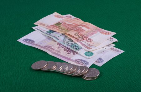 coins and bills lie on a green table, closeup photo, side view Фото со стока