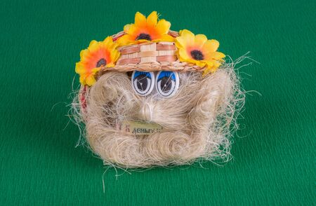 handmade brownie souvenir from braid fibers with an orange hat, closeup photo,