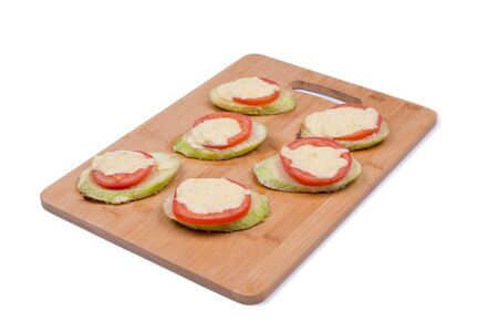 Slices of zucchini with tomatoes and cream cheese LAY ON A WOODEN BOARD FOR COOKING, OBJECT ISOLATED, BACKGROUND WHITE