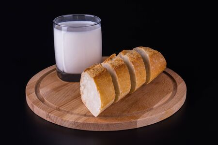 cutaway bread baguette and a glass of milk, black background, side view