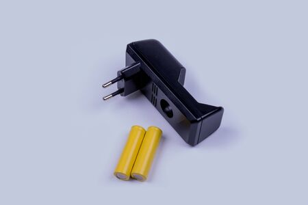 charger and two yellow batteries on a white background, side view