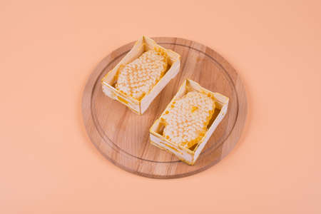 two portions of bee honey in honeycombs on a round wooden board, the object is isolated, the background is beige, top view