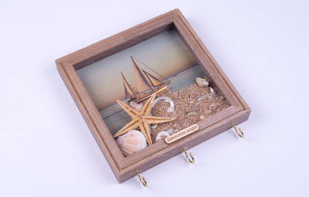 picture with key hooks in the form of an image of a sailing yacht at sea, object on a gray background Stock fotó