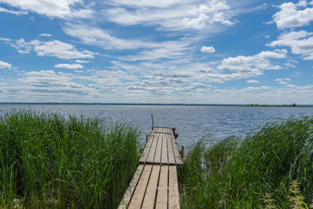 wooden pier by Lake Nero, on the sides there are reeds and a view of the lake, photo was taken on a sunny summer day