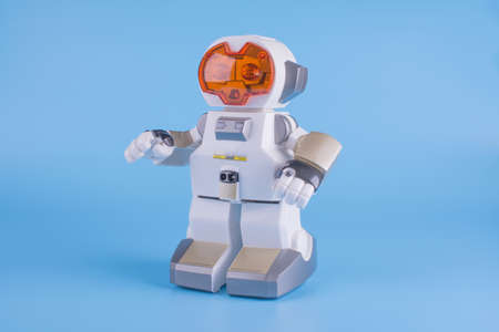 electronic, toy robot white with orange eyes on a blue background, close-up, side view