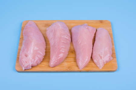 four chicken breasts lie in a row on a wooden board, background blue, top view Stock fotó