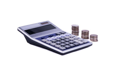calculator in the foreground and three stacks of coins in the background, the object is isolated on a white background, side view