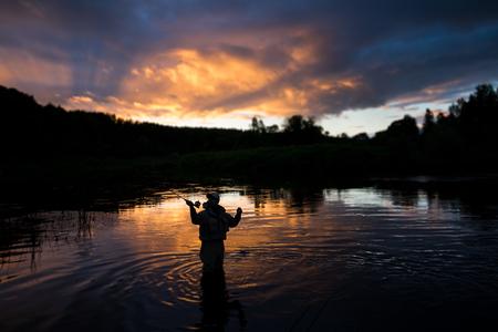 waders: El hombre pesca en el río con caña de mosca y limícolas Foto de archivo