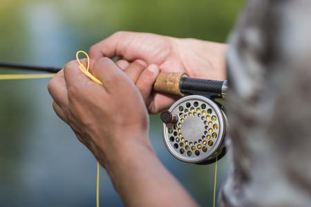 川沿いに彼の棒を鋳造のフライフィッシングします。