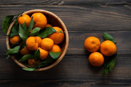 Tangerines - oranges, mandarins, clementines, citrus fruits, with leaves in basket over wooden background Stock Photo