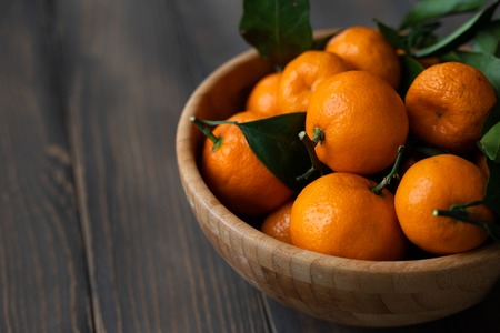 Tangerines - oranges, mandarins, clementines, citrus fruits, with leaves in basket over wooden background Reklamní fotografie