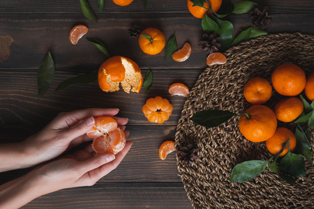 Female hands holding tangerine on wooden background. Good Wallpapers for smartphone Stock Photo
