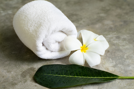 spa towel with plumeria on the grey stone table.