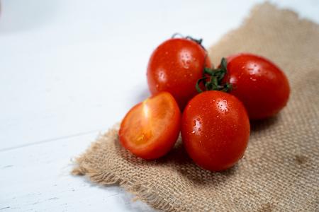 Fresh cherry tomatoes on a white wood background. 写真素材