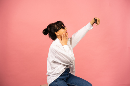 Young girl in sunglasses making selfie on a pink background. Stockfoto