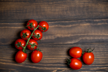 Fresh cherry tomatoes on a dark wood background.