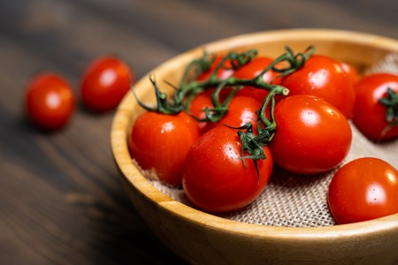 Fresh cherry tomatoes in a plate on a dark wood background.