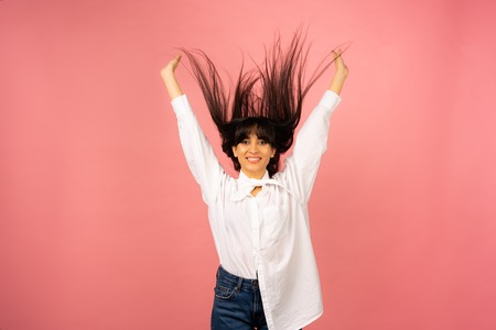 Young beautiful girl in a white shirt posing for a photo on a pink background.