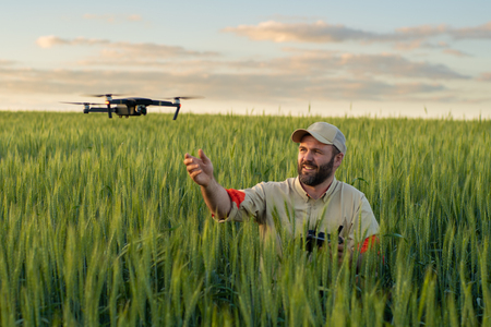 Athletic man and videographer in rye field catch drone on sunset background.
