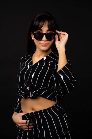 Young business girl in a black suit posing for a photo on a black background. Stockfoto