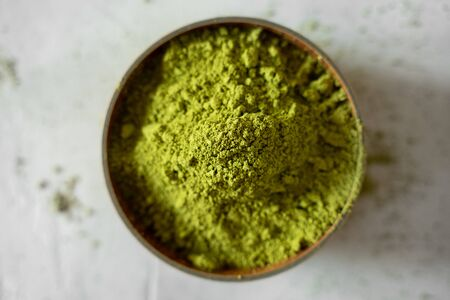 Matcha tea in a brown cup on a gray background