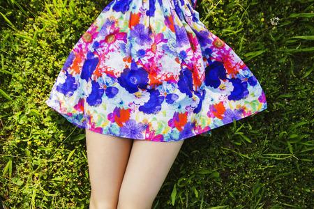 足と芝生で横になっている少女のカラフルなスカート