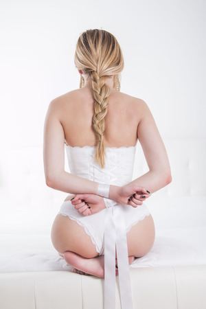 Sexy woman in white panties with hands tied from back Stock Photo