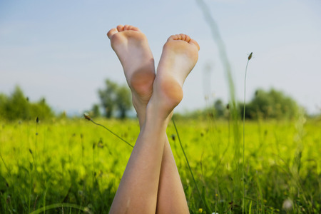 lying on leaves: Young girl chilling in the grass, with feet up