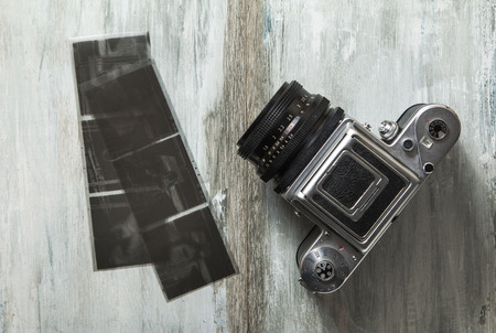 format: Old medium format camera and films on wooden table