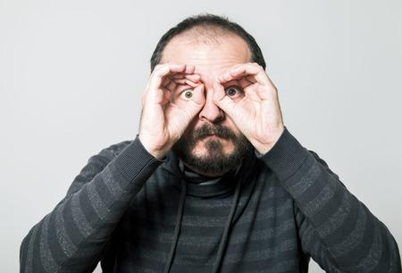 Shocked man looking through hands, making binoculars Stock fotó