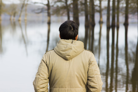 observing: Man in jacket observing the river Stock Photo