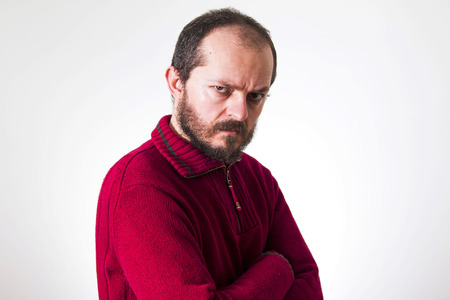 arrogance: Portrait of angry man, in red sweater, with beard and mustaches