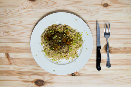 couscous: Moroccan couscous with apricots on natural wooden table
