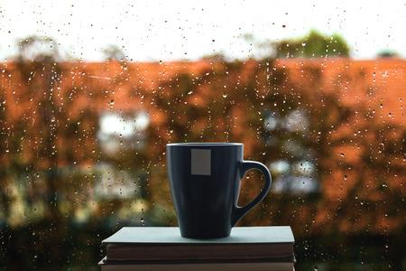 Boeken en koffie op het venster, regen druppels op glas in achtergrond Stockfoto