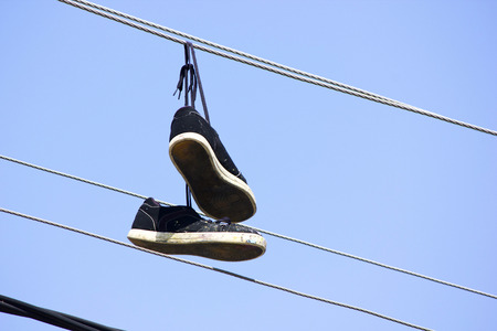 Old used sneakers hanging on wires in the air