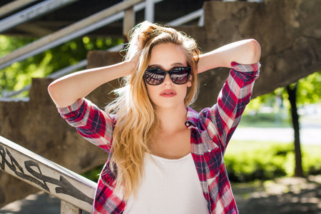 Portrait of trendy hipster girl with sunglasses and hands behind her head standing on the stairs outdoor. Youth street style. photo