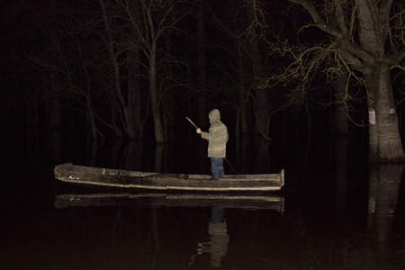 lost lake: Man standing in the boat on lake in night
